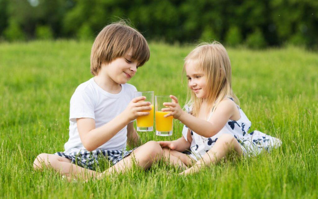 Дети пьют фруктовый сок