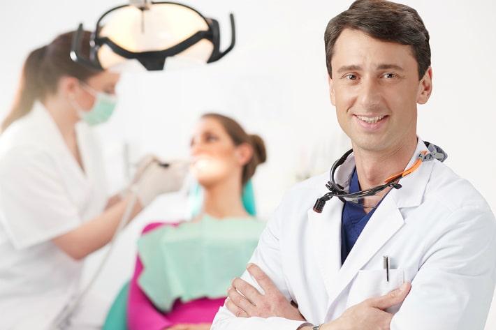 врач-стоматолог, который фиксирует съёмный протез