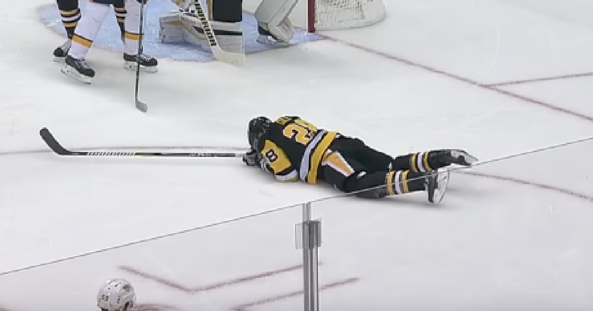 Хоккеист, лежащий на льду