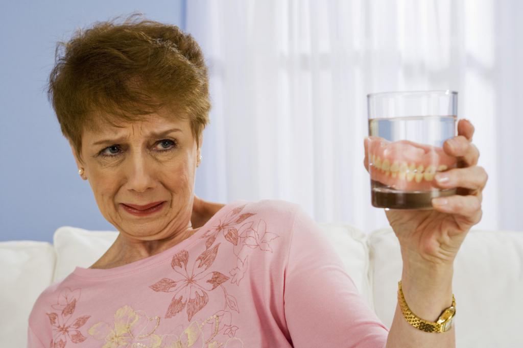 Женщина со стаканом с протезами