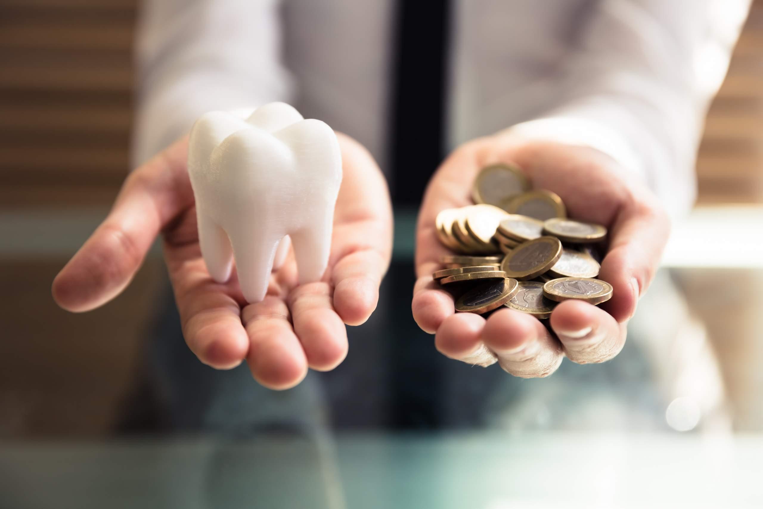 Зуб и монеты в руках
